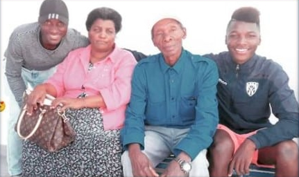 the midfielder, his parent and his sibling in a photo.