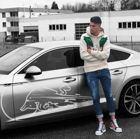 the player possing close to his brand new car.